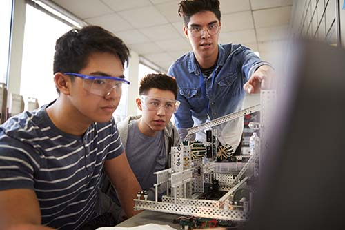 Teacher With Two College Students Building Machine In Science Robotics Or Engineering Class