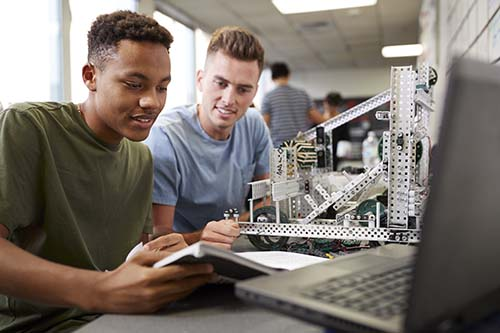 Two University Students Building Machine In Science Robotics Or Engineering Class